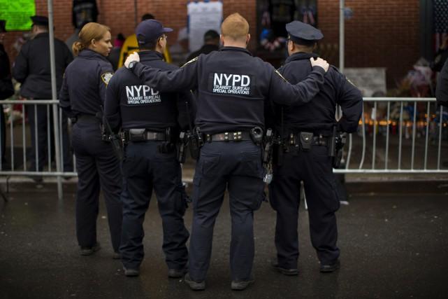 Des policiers se recueillent près d'un mémorial préparé... (Photo Mike Segar, Reuters)