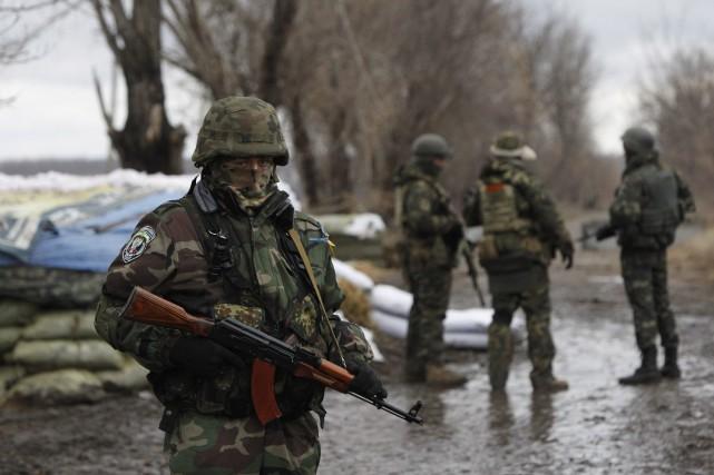 Des soldats ukrainiens gardent un point de contrôle... (Photo Sergei Chuzavkov, AP)
