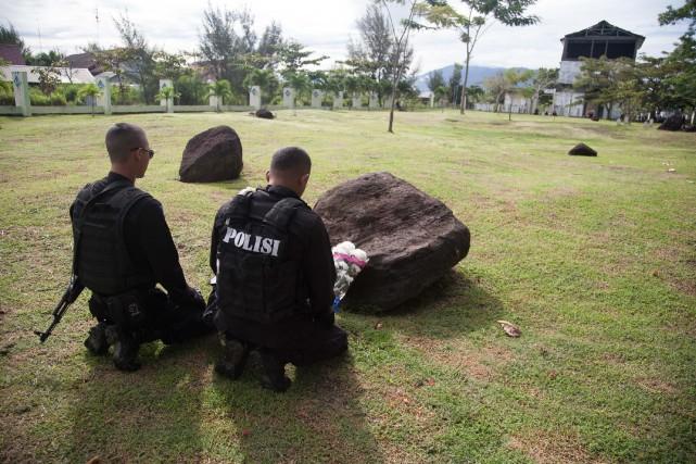 Deux policiers se recueillent dans le nord de... (Photo Chaideer MAHYUDDIN, AFP)