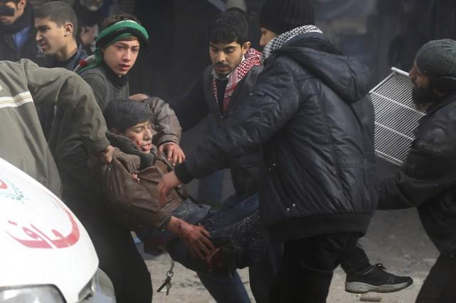 Des civils viennent en aide à un jeune... (PHOTO BASSAM KHABIEH, REUTERS)
