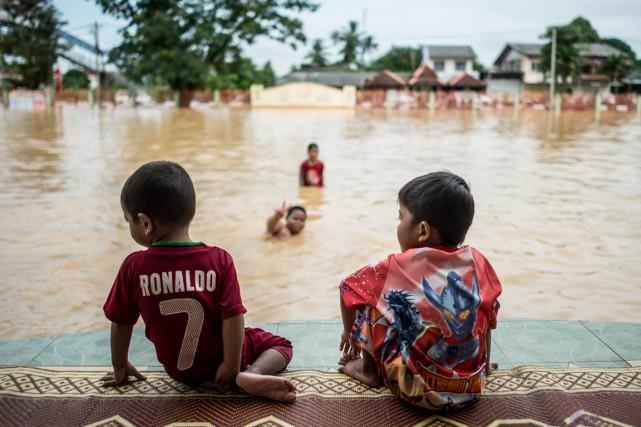 Deux garçons regardent un ami se baigner dans... (PHOTO MOHD RASFAN, AFP)