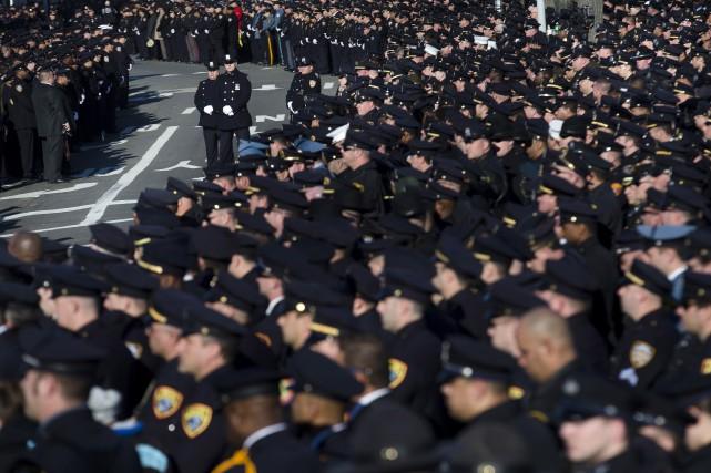 Les policiers assistent aux funérailles de l'un des... (Associated Press)