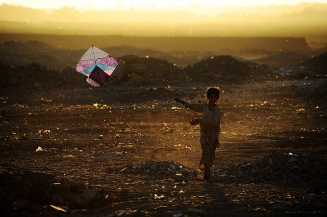 Un enfant afghan joue avec un cerf-volant dans... (PHOTO AREF KARIMI, AFP)