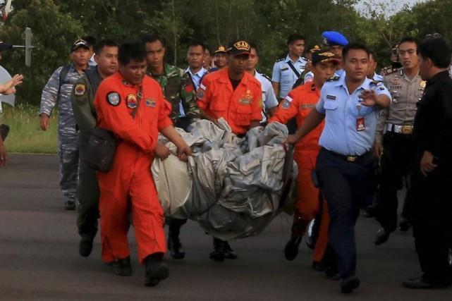 Des membres des équipes de recherches transportent des... (PHOTO REUTERS/Antara Foto/Kenarel)