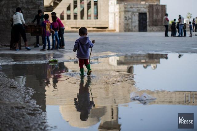 Un jeune réfugié syrien marche dans l'eau laissé... (PHOTO EDOUARD PLANTE-FRÉCHETTE, ARCHIVES LA PRESSE)