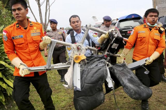 Des secouristes transportent deux sièges de l'épave du... (PHOTO TATAN SYUFLANA, AP)