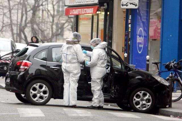Deux analystes de la police examinent un véhicule... (PHOTO AP)