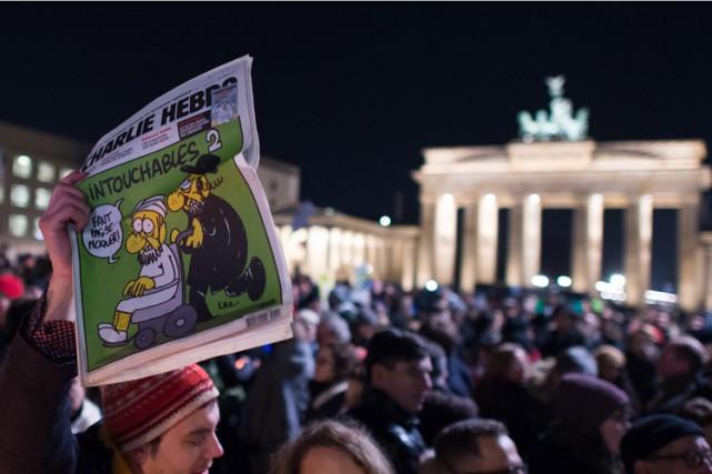 Un manifestant brandit un exemplaire de Charlie Hebdo... (Photo: AFP)