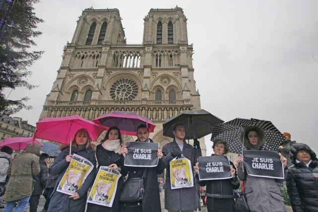 Des gens sous la pluie tenaient jeudi des... (AFP, Matthieu Alexandre)