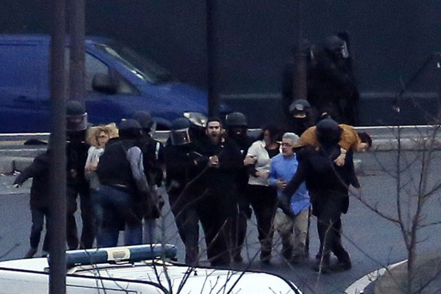 Des policiers d'élite évacuent les otages de l'épicerie... (PHOTO THOMAS SAMSON, AFP)