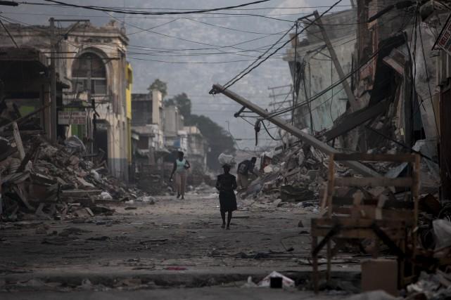 Une femme marche dans une rue de Port-au-Prince... (Associated Press)