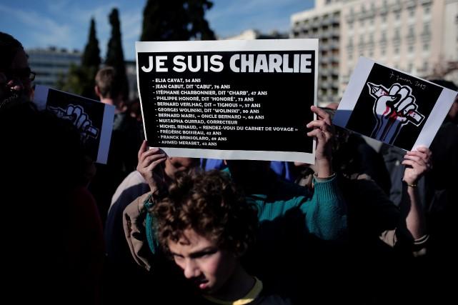 Une femme tient une affiche «Je suis Charlie»où... (AFP, Angelos Tzortizinis)