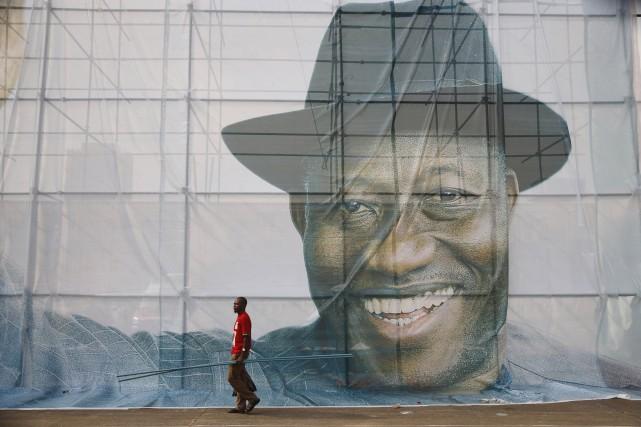 Un homme passe devant le portrait géant du... (Photo Akintunde Akinleye, Reuters)