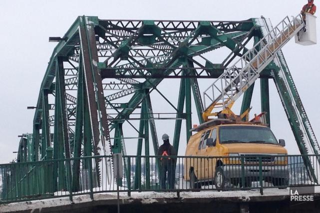 Des employés municipaux s'affairaient sur le pont de... ((Courtoisie))