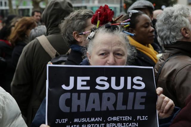 Une femme manifeste son appui à Charlie Hebdo... (PHOTO PHILIPPE WOJAZER, REUTERS)
