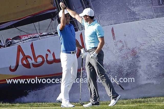 Rory McIlroy (à droite) célèbre avec son partenaire... (Photo Karim Sahib, AFP)