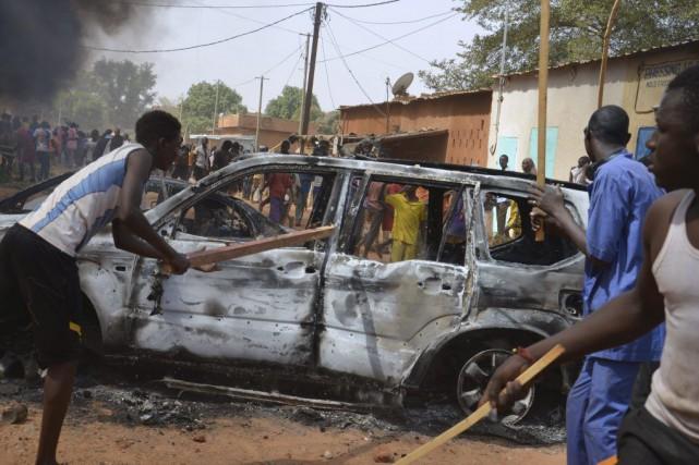 Des manifestants donnent des coups de bâton sur... (PHOTO BOUREIMA HAMA, AFP)