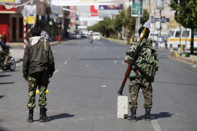 Des combattants houtis, lourdement armés, bloquent une rue... (PHOTO KHALED ABDULLAH, REUTERS)
