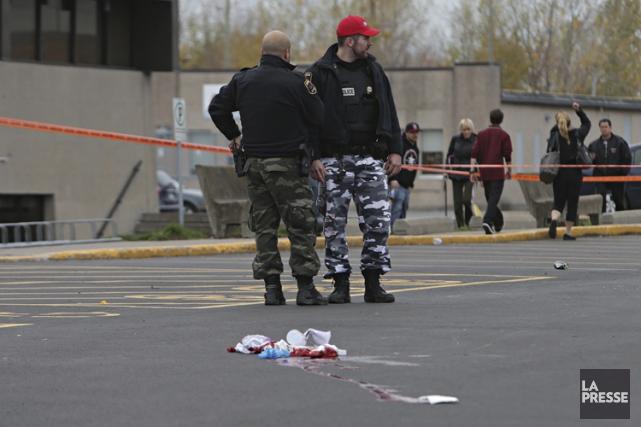 Des policiers examinent la scène où Couture-Rouleau a... (PHOTO PATRICK SANFAÇON, ARCHIVES LA PRESSE)