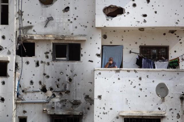Un homme est vu sur le balcon de... (PHOTO KHALIL HAMRA, ARCHIVES AP)