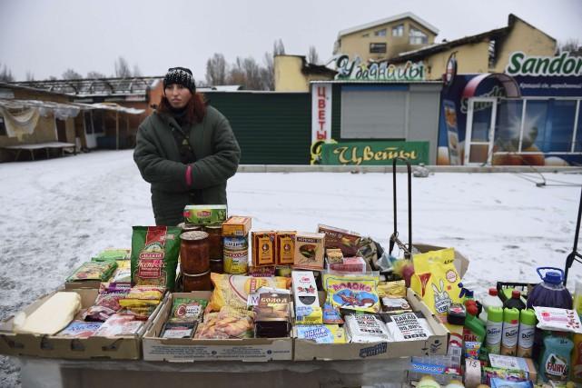 Une femme vend des marchandises près d'un marché... (PHOTO ERIC FEFERBERG, AFP)