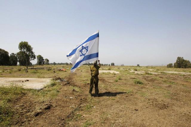 Un soldat de Tsahal plantant un drapeau israélien... (PHOTO BAZ RATNER, ARCHIVES REUTERS)