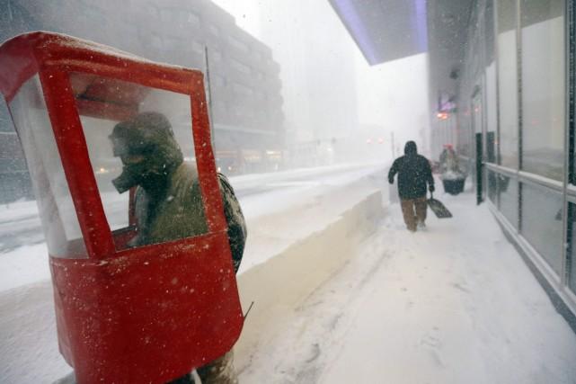 Un homme marche dans les rues enneigées de... (PHOTO STEVEN SENNE, ASSOCIATED PRESS)