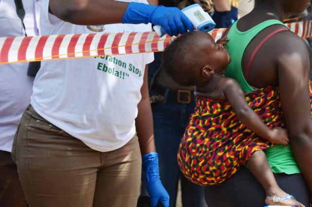 Un intervenant médical vérifie la température d'une fillette... (PHOTO ZOOM DOSSO, ARCHIVES AFP)