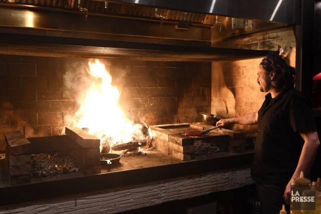 On prépare des grillades au-dessus d'un immense feu... (PHOTO BERNARD BRAULT, LA PRESSE)
