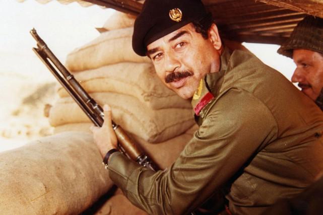 L'ex-dictateur irakien Saddam Hussein, fusil à la main,... (Archives AFP)