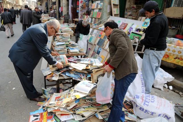 À Bagdad, des hommes regardent livres et magazines,... (PHOTO KARIM KADIM, ARCHIVES AP)