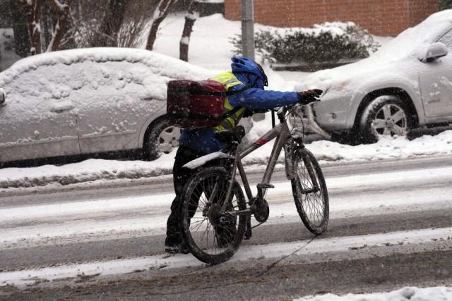 Un livreur pousse son vélo dans les rues... (PHOTO JEWEL SAMAD, AFP)