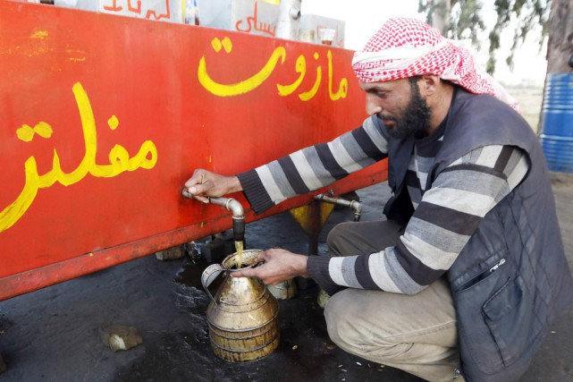 Un vendeur remplit une cruche de diesel, à... (PHOTO ARCHIVES REUTERS/STRINGER)