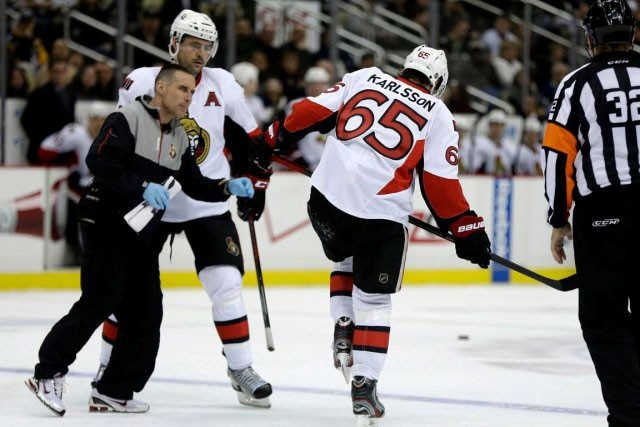 Erik Karlsson quittant la patinoire de peine et... (Archives, Associated Press)