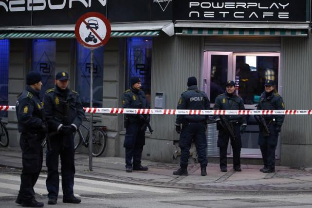 Des policiers sont postés devant un café internet... (Photo: Reuters)