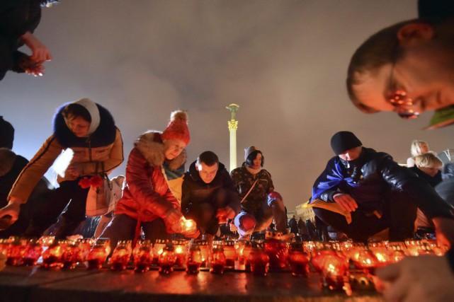 Des Ukrainiens ont allumé des bougies vendredi pour... (PHOTO SERGEI SUPINSKY, AFP)