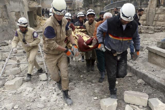 Des secouristes transportent une femme de 80 ans... (PHOTO FADI AL-HALABI, AFP)