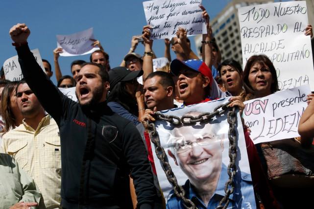 Des manifestants, dont un tient une affiche à... (PHOTO ALEJANDRO CEGARRA, ARCHIVES AP)