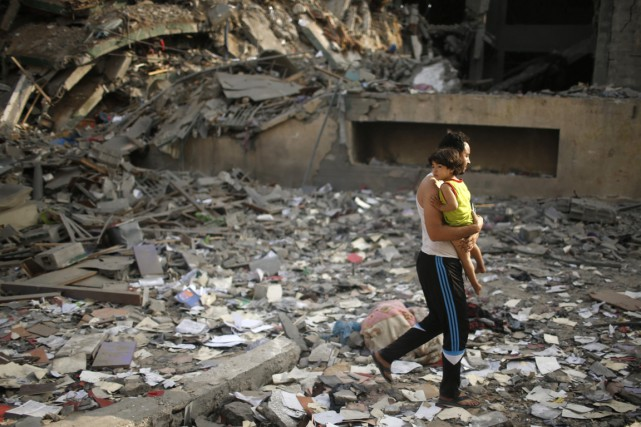 Un Palestinien et son fils dans les ruines... (PHOTO MOHAMMED SALEM, ARCHIVES REUTERS)