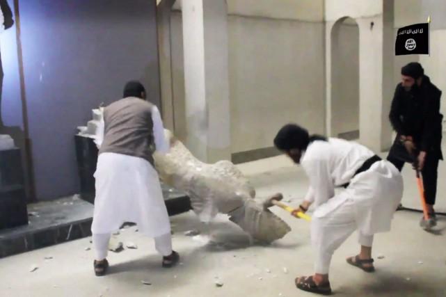 À coups de marteaux, les extrémistes de l'EI... (PHOTO AP)