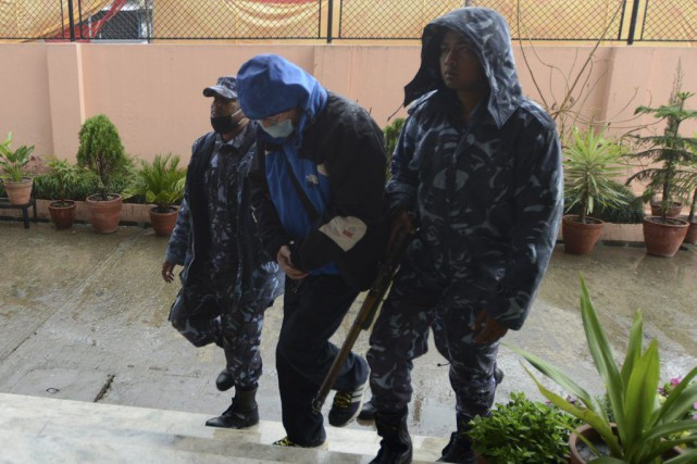 Des policiers escortent Ernest Fenwick MacIntosh (au centre)... (PHOTO PRAKASH MATHEMA, AFP)