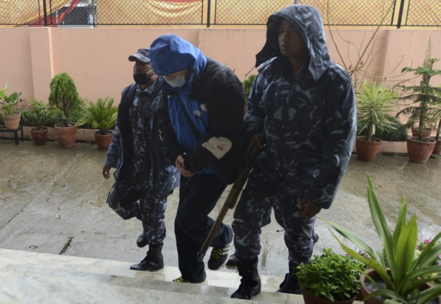La police népalaise escorteErnest Fenwick MacIntosh, 71 ans,... (Photo AFP, Prakash Mathema)