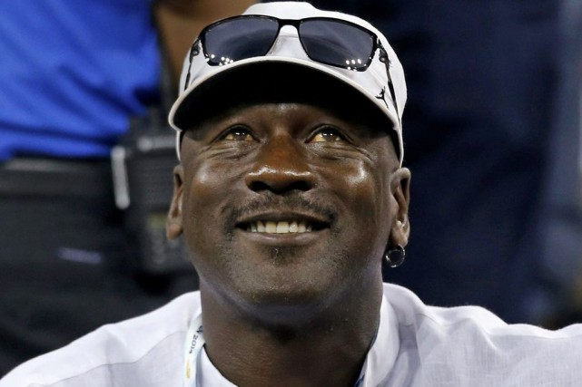 Former basketball great Michael Jordan watches a match... (SHANNON STAPLETON)