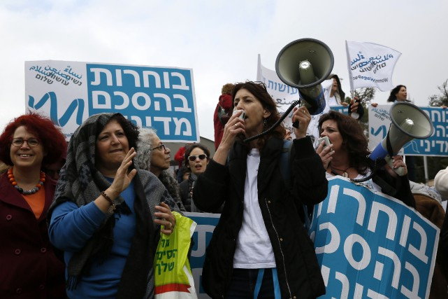 Malgré la pluie intermittente, les membres du mouvementWomen... (PHOTO GALI TIBBON, AFP)