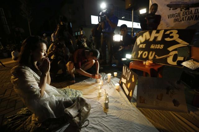La femme d'un passager du vol MH370 priait... (PHOTO VINCENT THIAN, AP)