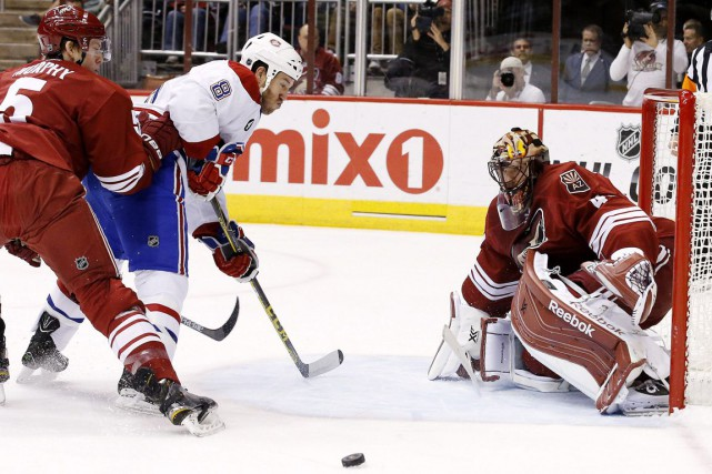 Mike Smith se signale contre Brandon Prust.... (Photo Ross D. Franklin, AP)