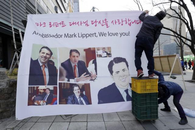 Des Sud-coréens installent une bannière montrant des portraits... (PHOTO AHN YOUNG-JOON, AP)