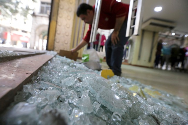 Un travailleur ramasse des débris de verre à... (PHOTO MOHAMED ABD EL GHANY, ARCHIVES REUTERS)