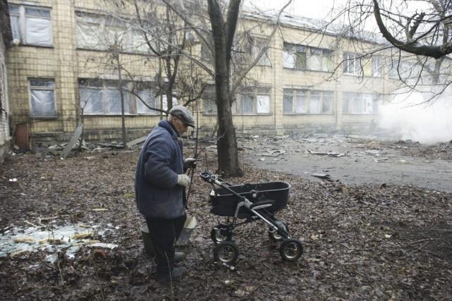 Un travailleur récupère des débris à l'extérieur d'un... (PHOTO JOHN MACDOUGALL, AFP)