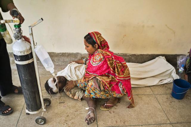 Une femme est au chevet de son mari... (PHOTO SHAIKH MOHIR UDDIN, AP)